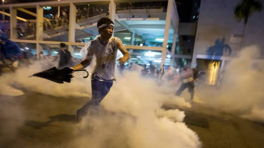 A protester throws an umbrella at riot police as fellow demonstrators blocked the main street to the financial district outside government headquarters in Hong Kong Sept. 29, 2014.