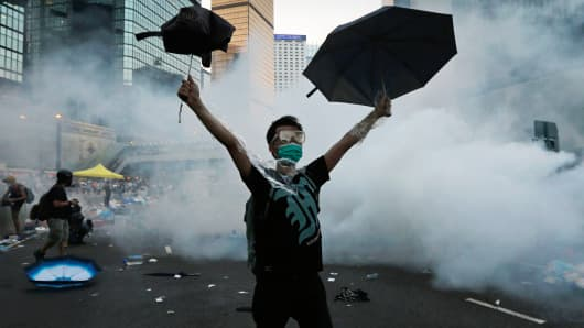 A protester raises his umbrellas in front of tear gas which was fired by riot police to disperse protesters in Hong Kong, September 28, 2014.