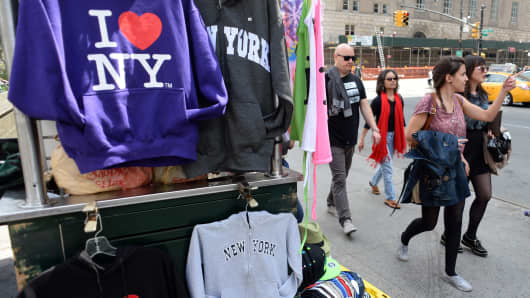 Tourists pass a shirt vendor on 59th Street in New York.