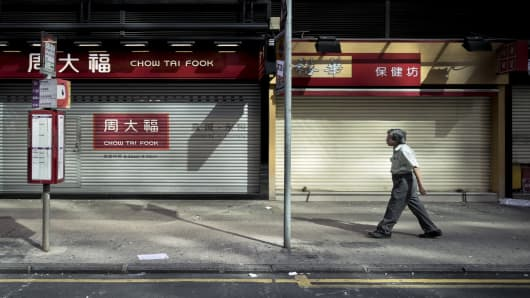 A man walks past shuttered stores as a pro-democracy protest gathers on Nathan Road, a major route through the heart of the Kowloon district of Hong Kong, on September 29, 2014.