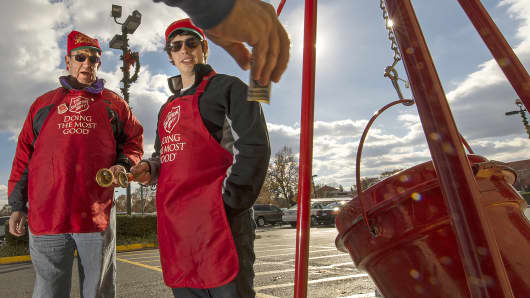 Salvation Army volunteers ring their bells as a donation is put into a kettle in Clifton, Va.