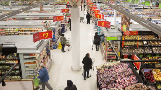 Customers look for groceries as they push shopping carts along the shopping aisles inside an Asda supermarket in London.