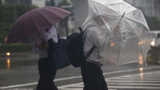 Passers-by with umbrellas struggle against strong winds and heavy rain caused by Typhoon Phanfone, in Tokyo October 6, 2014.