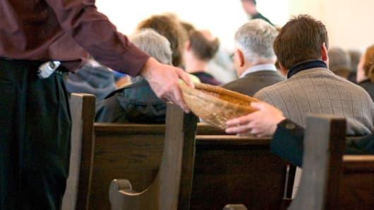 Passing collection basket in church, religious charity, religious philanthropy
