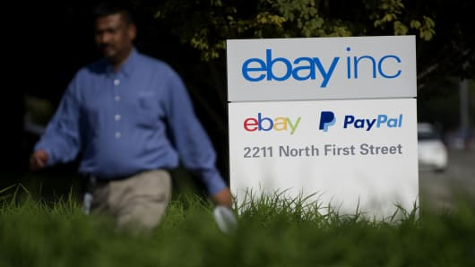 A pedestrian walks past eBay Inc. signage displayed at the company's headquarters in San Jose, California.