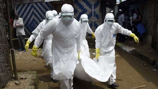 Red Cross workers carry away a person suspected of dying from Ebola, in the Liberian capital Monrovia, on Oct. 4, 2014.