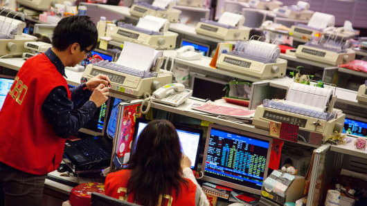 Traders work on the floor of the Hong Kong Stock Exchange.