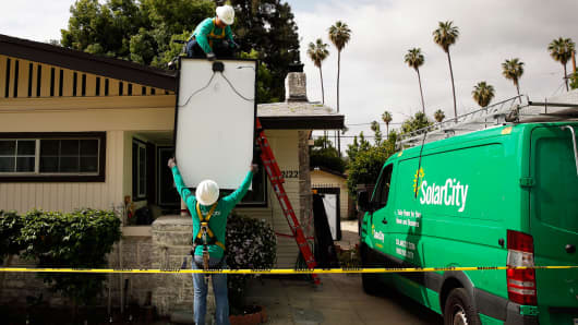 SolarCity employees lift solar panels onto the roof of a home in Los Angeles.