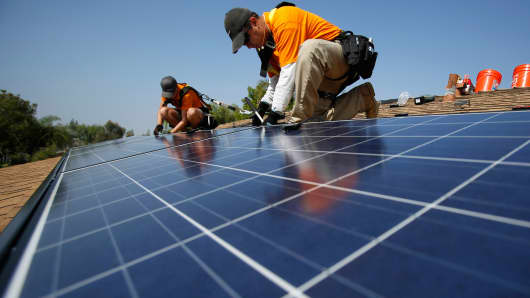 Technicians install solar panels on a house in Mission Viejo, Calif.