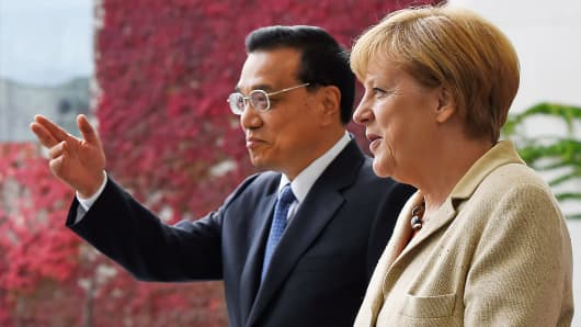 Chinese Premier Li Keqiang gestures while standing beside German Chancellor Angela Merkel during an official welcoming ceremony at the Chancellery in Berlin Oct. 10, 2014.