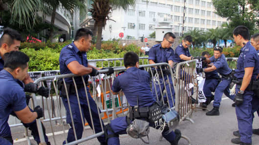 Police officers remove barricades from pro-democracy demonstrators (unseen) near the government offices in Hong Kong.