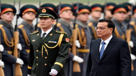 Chinese Prime Minister Li Keqiang (on right) reviews an honor guard during an official welcoming ceremony at Vnukovo airport outside Moscow on October 12, 2014.