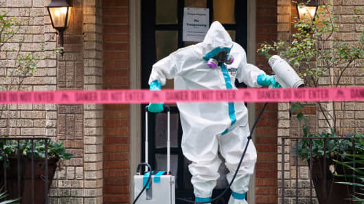 A member a HazMat team disinfects the entrance to the home of the Texas nurse who contracted Ebola from a patient.
