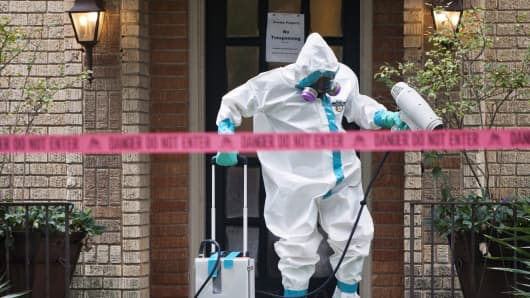 A member of the CG Environmental HazMat team disinfects the entrance to the residence of a health worker at the Texas Health Presbyterian Hospital who has contracted Ebola in Dallas, Texas, October 12, 2014.