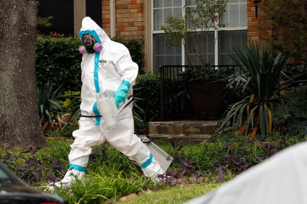 A man dressed in protective hazmat clothing walks towards an apartment where a second person diagnosed with the Ebola virus resides on October 12, 2014 in Dallas, Texas.