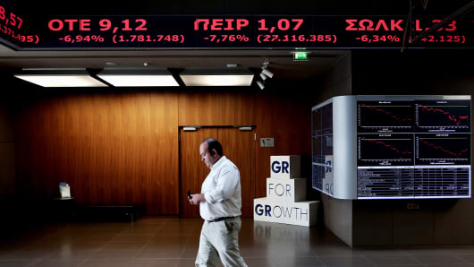 A visitor walks beneath a display at the Athens Stock Exchange, Oct. 15, 2014.