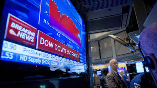 A screen displays news on the Dow Jones Industrial Average on the floor of the New York Stock Exchange, Oct. 15, 2014.