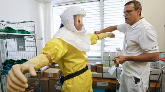 Infection control nurse Marc Dangel, right, assists colleague Heinz Schuhmacher with a protection suit during a media presentation at an isolation ward for possible Ebola patients at of the Universitaetsspital Basel hospital in Basel, Switzerland.