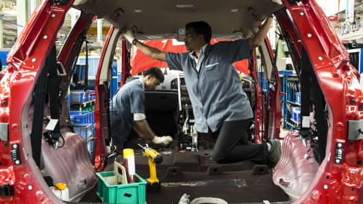 Employees install interior panels and fittings to a Mahindra & Mahindra XUV 500 sport-utility vehicle (SUV) on the production line at the company's facility in Chakan, Maharashtra, India.