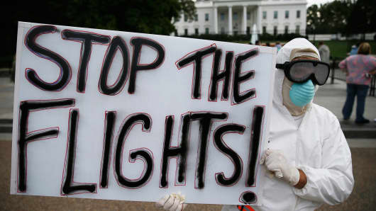Protester holds a sign reading Stop the Flights in front of the White House, October 16, 2014.
