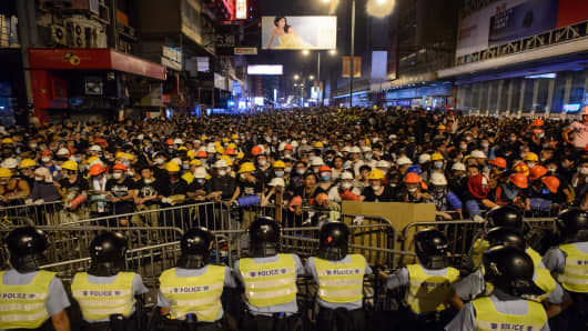 Pro-democracy protesters and police standoff on a street in the Mong Kok district of Hong Kong early on October 19, 2014.