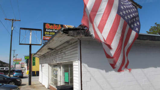 A tattered American flag waves from a storefront in Jacksonville, N.C.