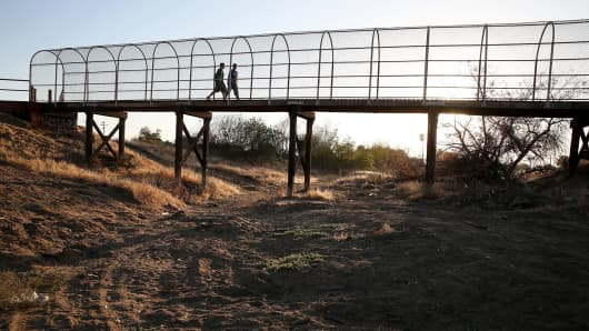 A footbridge spans a dry river bed in Porterville, Calif.