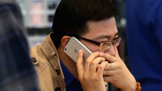 A Chinese man answers the phone with his new iPhone 6 Plus inside an Apple store on October 17, 2014 in Beijing, China.