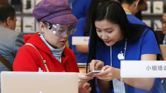 A woman sets up her new iPhone 6 with the help of an Apple store employee inside an Apple store on October 17, 2014 in Beijing, China.