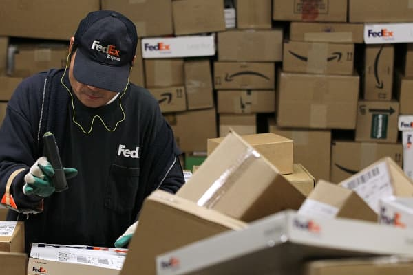 A FedEx worker scans a pile of boxes at a FedEx sort facility.