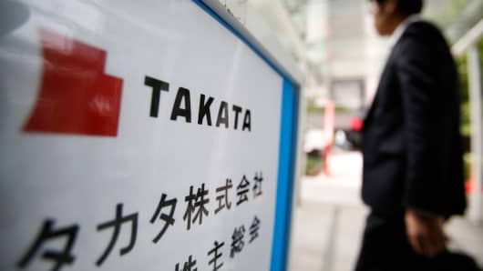 A man walks past a sign board of Japanese auto parts maker Takata Corp's Annual General Meeting in Tokyo June 26, 2014.
