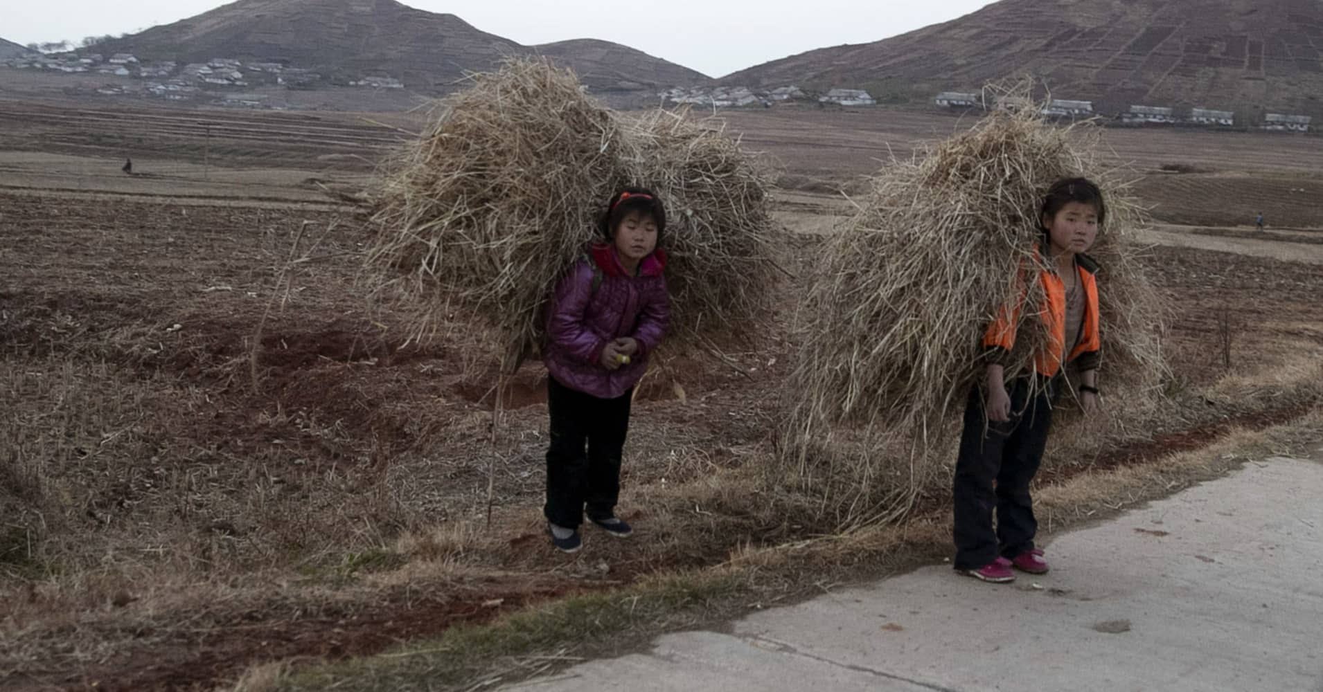 North Korean children carry hay on a road near Mount Kuwol in South Hwanghae province, North Korea.