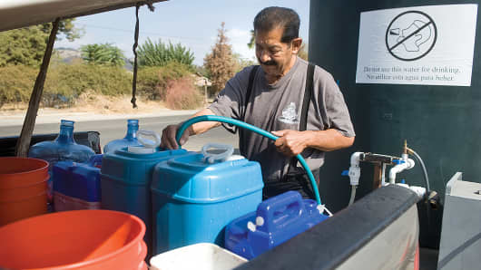 Tony Alvarez fills water containers at Tulare County Fire Station 20 in Porterville, Calif., Oct. 21, 2014.