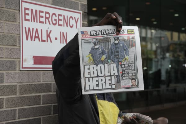 A newspaper vendor holds up today's issue outside Bellevue Hospital after the first patient was diagnosed in New York City.
