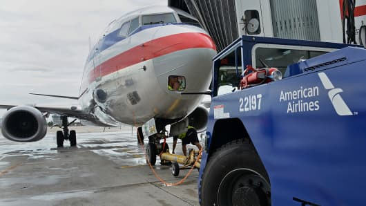 A ground crewmember prepares to push back an American Airlines Boeing 737-823 jet at a terminal at  Miami International Airport.