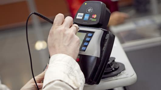 A customer signs her name on a credit card machine while checking out at a BJ's Wholesale Club store in Falls Church, Va.