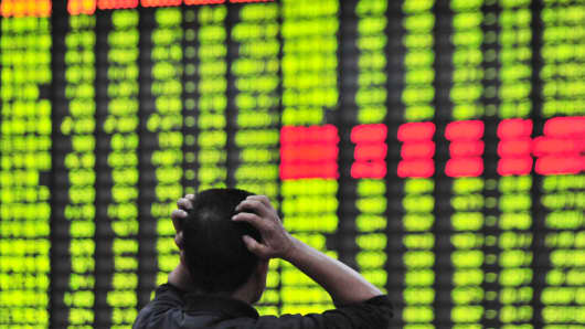 An investor watches the electronic board at a stock exchange hall in Jiujiang, China.