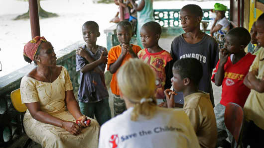 Carolyn Miles, foreground, president and chief executive officer for Save the Children, listens to orphans in Unification Town, Liberia, October 3, 2014.