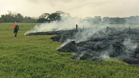 A Hawaii Volcano Observatory geologist maps the margin of the lava flow from the Kilauea Volcano October 26, 2014.