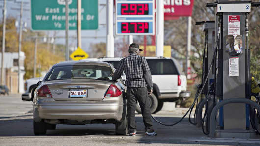 Gas prices are displayed as a customer fuels a vehicle at a Mobil gas station in Peoria, Ill., Oct. 29, 2014.
