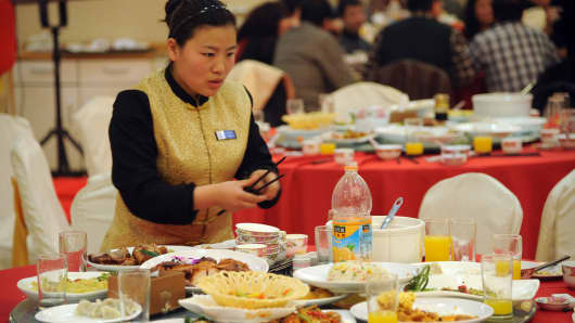 A waitress clean a table of dishes in Taiyuan, Shanxi Province of China.
