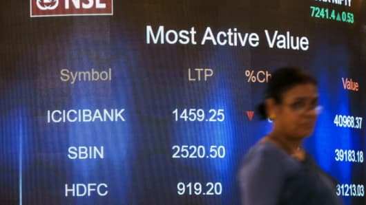 An employee walks past an electronic board that indicates the latest stock figures at the National Stock Exchange (NSE) in Mumbai, India, on Monday, May 19, 2014.