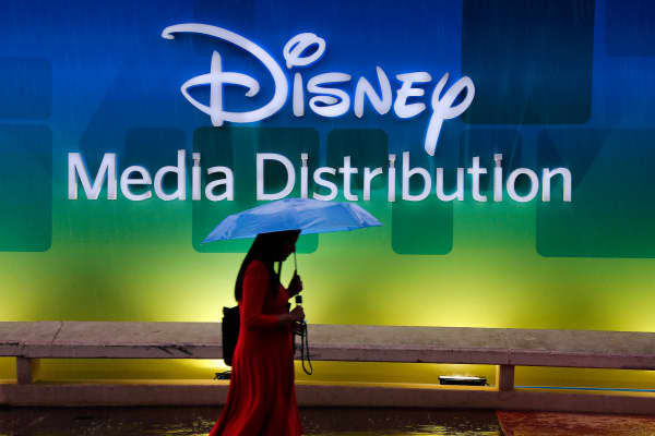 A visitor walks past a poster of Disney Media Distribution during the annual MIPCOM television program market in Cannes, France, October 13, 2014.