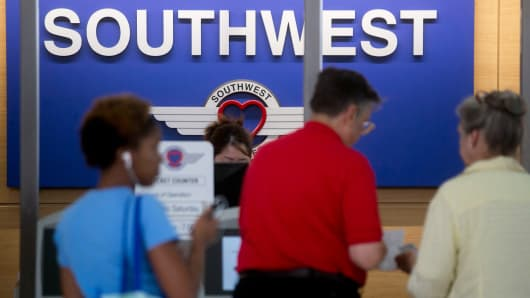 Travelers receive boarding passes at the Southwest Airlines check-in counter at Ronald Reagan National Airport in Washington.