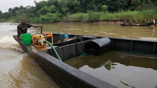 File photo: A suspected oil thief rides a wooden boat full of stolen crude oil on the creeks of Bayelsa, Nigeria