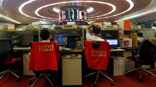 Floor traders monitor share prices during afternoon trading at the Hong Kong Stock Exchange.