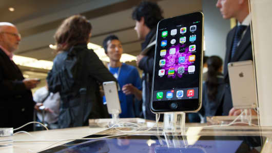 An iPhone 6 Plus on display in an Apple store as customers talk with a salesperson.