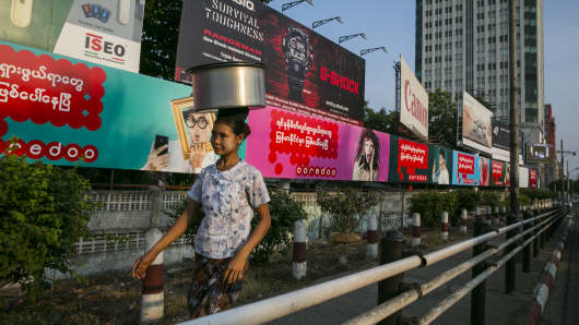 A Burmese woman walks by billboards in Yangon, Myanmar.
