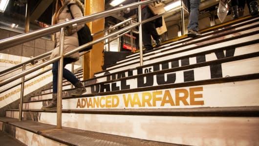 People on staircase with ad for Call of Duty: Advanced Warfare in New York.