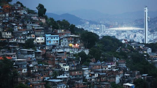 Rio's iconic Maracana Stadium lit at dusk behind a shanytown.